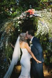 Bride and groom announced as husband and wife, kiss under the flower arbor